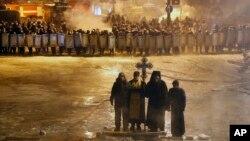Những tu sĩ Chính thống giáo Ukraine đóng vai trò tích cực trong những cuộc biểu tình ở Kiev. Trong ảnh, một tu sĩ đang cầu nguyện cạnh 2 người biểu tình ủng hộ châu Âu trong một buổi sáng lạnh lẽo, ngày 24 tháng 1, 2014