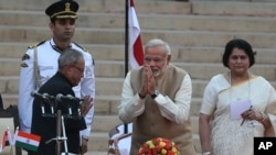 India's new Prime Minister, Narendra Modi, center, greets President Pranab Mukherjee, left, after taking the oath of office at the presidential palace in New Delhi, India, May 26, 2014.
