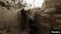 Free Syrian Army fighters take their positions behind piled sandbags, as one of them points his weapon, from inside a room in Deir al-Zor, Sept. 2, 2013.