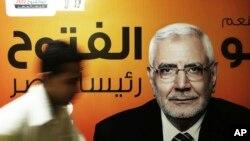 Pada foto 19 Mei 2012,seorang petugas kampanye berjalan di depan poster kandidat presiden Mesir, Abdel-Monaem Abul Fetouh di markasnya di Kairo, Mesir. Abdel-Monaem ditahan pada 15 Februari 2018 karena diduga berhubungan dengan Kelompok Persaudaraan Muslim yang terlarang.
