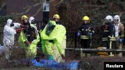 Agentes son ayudados a sacarse los trajes protectores tras reubicar la tienda de campaña forense colocada sobre la banca de Salisbury, Gran Bretaña, donde fueron encontrados un exespía ruso y su hija. Marzo 8 de 2018.
