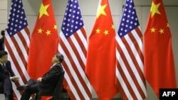 两名男子在大阪G20峰会期间会场摆放的美中国旗前聊天。(2019年6月29日)