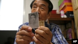 In this Aug. 17, 2018, photo, Lee Soo-nam shows photos of his brother Ri Jong Song in North Korea during an interview at his home in Seoul. Lee is among about 200 war-separated S. Korean and their family members who are crossing into N. Korea for heart-wrenching meetings with relatives they haven't seen for decades.