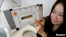 Kumi Goto, karyawan perusahaan pembuat toilet papan atas di Jepang, Toto Limited, memeragakan cara menggunakan toilet dengan teknologi baru, di Tokyo, 1 Februari 2005. (Foto:dok)