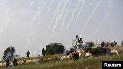 Des manifestants palestiniens fuient les obus de gaz lacrymogènes lancés par les troupes israéliennes lors d'affrontements suite à une manifestation marquant la Journée de la Terre, dans le village de Nabi Saleh, en Cisjordanie, près de Ramallah le 28 mars 2015.