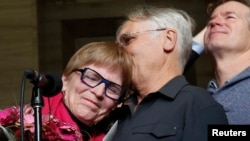 Lee Carter, whose mother had challenged Canada's assisted-suicide ban and traveled to Switzerland to end her life in 2010, embraces her husband, Hollis Johnson, while speaking to journalists at the Supreme Court of Canada in Ottawa, Feb. 6, 2015.