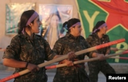 FILE - Kurdish female fighters of the Women's Protection Unit (YPJ) participate in training at a military camp in Ras al-Ain city in Syria's Hasakah province, June 30, 2014.