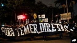 "Demonstrators protest holding a banner that reads in Portuguese ""Get out Temer, elections now,"" outside the residence of Brazil's President Michel Temer during a general strike in Sao Paulo, Brazil, April 28, 2017."
