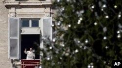 El papa Francisco saluda desde el balcón durante la oración del Angelus, con el árbol de Navidad del Vaticano en primer plano.