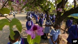 Schoolchildren wait to enter their school in Harare, Zimbabwe, Monday Sept, 28, 2020. Zimbabwe schools have reopened in phases, but with smaller number of pupils, more teachers and other related measures to enable children to resume their education withou