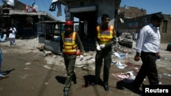 Rescue workers and journalists are seen outside the election campaign office of candidate Nasir Khan Afridi that was damaged in a bomb blast in Peshawar April 28 , 2013.