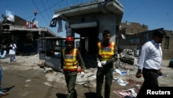 Nhân viên cứu hộ và các nhà báo bên ngoài văn phòng vận động bầu cử của ứng cử viên Nasir Khan Afridi, bị hư hại trong vụ nổ bom ở Peshawar, ngày 28/4/2013.