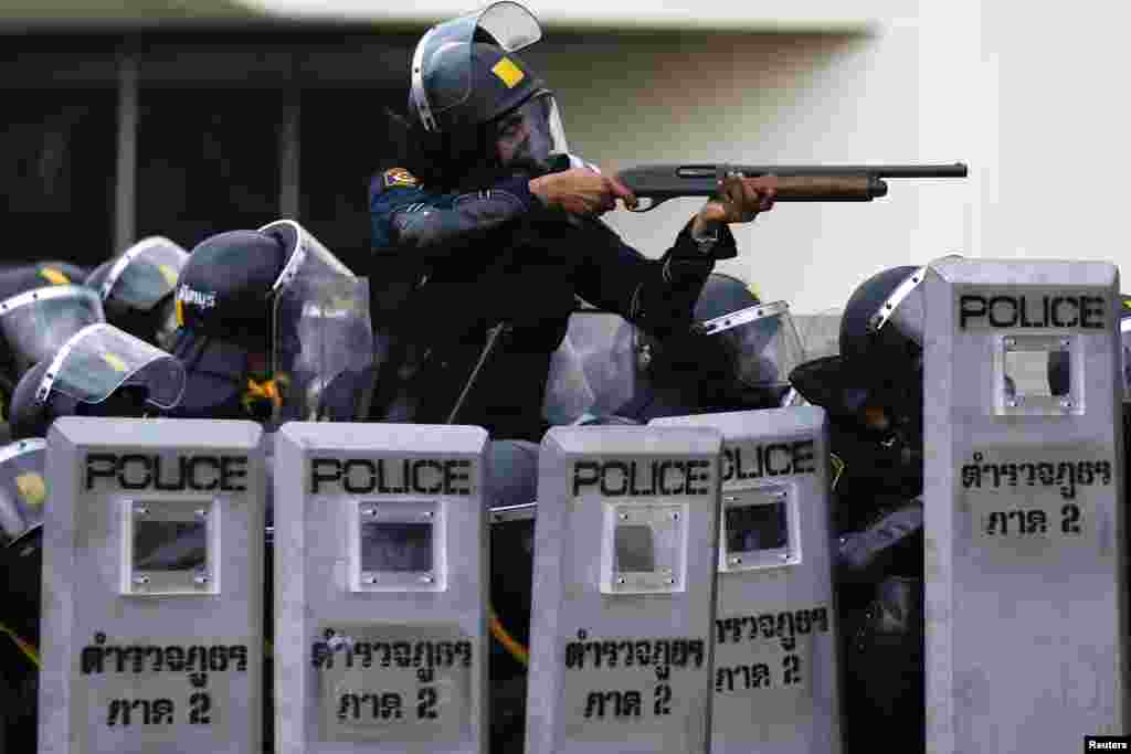 A policeman aims his weapon towards anti-government protesters during clashes near the Government House, Bangkok, Feb. 18, 2014.