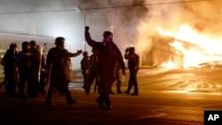 24일 미국 미주리주 퍼거슨 시에서 마이클 브라운을 사살한 경관에 대해 불기소 결정이 내려진 후, 시위대 항의로 불에 탄 건물 주변을 경찰이 순찰하고 있다.