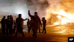 Police guard the area as some buildings are set on fire after the announcement of the grand jury decision, in Ferguson, Missouri, Nov. 24, 2014. (AP Photo/David Goldman)