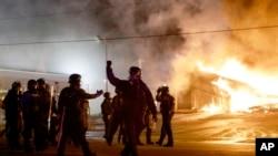 Polisi mengamankan kota Ferguson, Missouri sementara demonstran membakar sebuah gedung di sana, Senin (24/11).