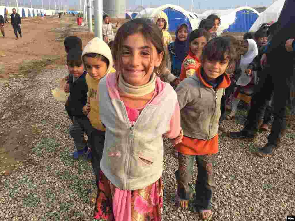 Anak-anak perempuan di Kamp Khazir, wilayah Kurdi di Irak, mengatakan mereka suka berpura-pura para pekerja kamp memberikan mereka kertas untuk mendapatkan pasokan seperti makanan dan bahan bakar (1/12). (VOA/H.Murdock)