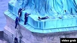 Cảnh sát New York trèo lên chân tượng Nữ thần Tự do để bắt giữ người phụ nữ tìm cách trèo lên cao để phản đối chính sách di trú của Tổng thống Donald Trump hôm 4/7.