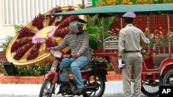 FILE PHOTO - A Cambodian police officer, right, talks with a motorcycle taxi driver next to a floral decoration set up ahead of the ASEAN Summit along a road in Phnom Penh, Cambodia, Sunday, April 1, 2012.