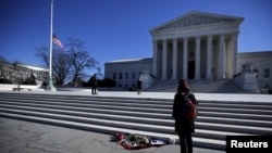 Flowers are seen as a woman stands in front of the Supreme Court building in Washington, D.C., after the death of U.S. Supreme Court Justice Antonin Scalia, Feb. 14, 2016.