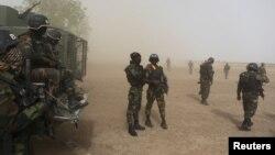 Des soldats camerounais de la Brigade d'intervention rapide montent la garde au milieu de la poussière soulevée par un hélicoptère en Kolofata, le Cameroun, le 16 Mars 2016 REUTERS / Joe Penney