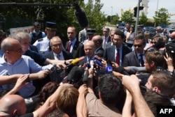 French Interior Minister Bernard Cazeneuve, center, speaks to the media near the entrance of the U.S.-based Air Products gas factory in Saint-Quentin-Fallavier, near Lyon, southeastern France, on June 26, 2015.