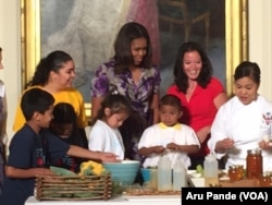 """Michelle Obama, center, and Deb Eschmeyer, second from right, head of """"Let's Move!"""" program, join kids in making salads from products out of the garden planted on the South Lawn of the White House earlier this year, June 3, 2015.er this year."""