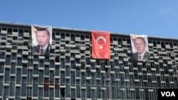 ຮ່ອງຮອຍຂອງການມີອຳນາດເພີ່ມຂຶ້ນ ຂອງປະທານາທິບໍດີເທີກີ ທີ່ຮູບພາບຂອງທ່ານ Recep Tayyip Erdogan ໄດ້ຖືກນຳໄປຕິດແທນຮູບທ່ານ Mustafa Kemal Ataturk, ຜູ້ກໍ່ຕັ້ງເທີກີ ສະໄໝໃໝ່ຊຶ່ງເປັນທີ່ເຄົາລົບຂອງຜູ້ຄົນ ທີ່ຕຶກສາທາລະນະ (L. Ramirez/VOA)
