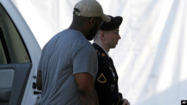 Army Pfc. Bradley Manning, right, is escorted into a courthouse in Fort Meade, Maryland, before a court martial hearing, July 18, 2013.