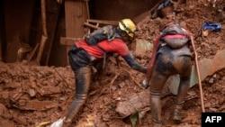 Para petugas pemadam kebakaran mencari korban yang tertimbun tanah longsor di Vila Bernadete, Belo Horizonte, negara bagian Minas Gerais, Brazil, 26