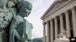 FILE - A cherub holding an open book adorns a flagpole on the plaza of the Supreme Court in Washington, April 4, 2016.