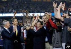 El presidente de los Medias Rojas de Boston, Tom Werner, sostiene el trofeo del campeonato mientras el presidente Sam Kennedy, tercero desde la derecha, el gerente Alex Cora, segundo desde la derecha y el lanzador Chris Sale, derecha, celebran después del Juego 5 de la Serie Mundial de béisbol contra los Dodgers de Los Angeles. Octubre 28 de 2018. AP