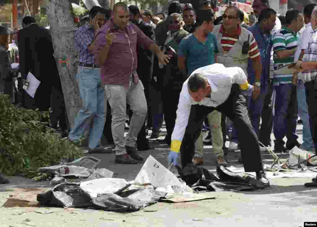 ماموران پزشکی قانونی و افسران پليس محل انفجار را بازرسی می کنند.