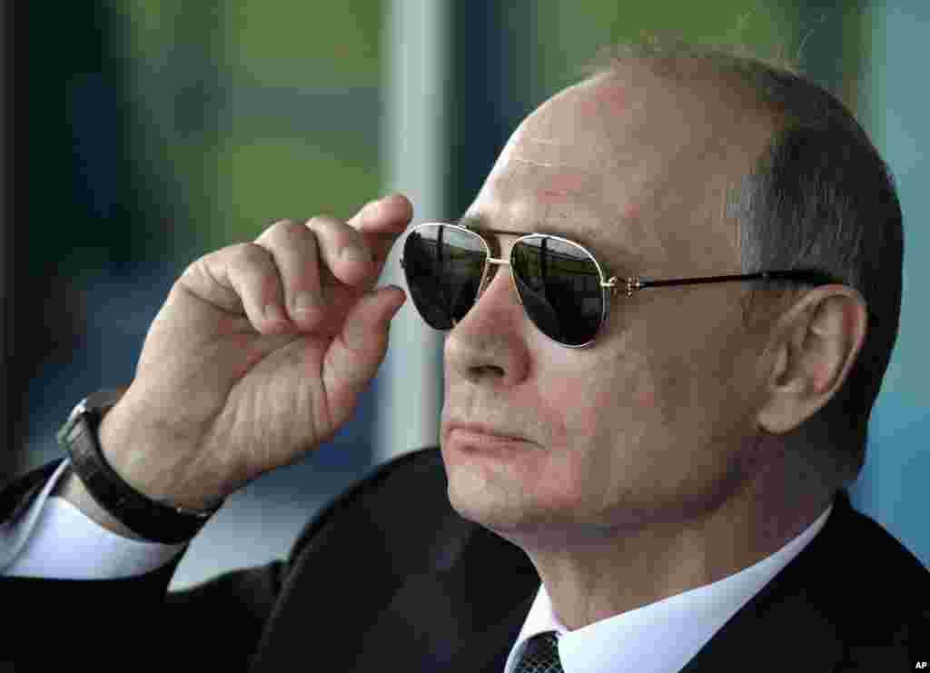 Presiden Rusia Vladimir Putin menonton aksi aerobatik angkatan udara Rusia di Zhukovsky, di luar kota Moskow.