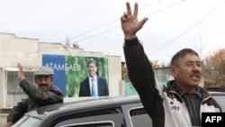 Local residents gesture, with a poster displaying Kyrgyzstan's Prime Minister and presidential candidate Almazbek Atambayev, in the village of Arashan outside the capital Bishkek October 26, 2011. Twenty candidates will vie for the presidency of Kyrgyzsta
