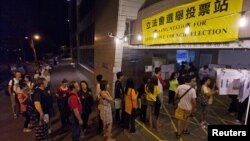 People queue as they wait to cast their votes at a polling station in Hong Kong on September 9, 2012.