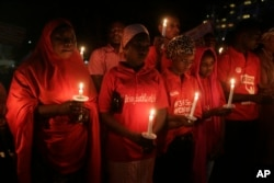 FILE - People hold candles during a vigil to mark the one year anniversary of the abduction of girls studying at the Chibok government secondary school, Abuja, Nigeria, April 14, 2015.