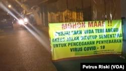 Salah satu kampung di Surabaya memasang portal jelang PSBB, yang membatasi keluar masuknya warga untuk mencegah penyebaran virus corona, Sabtu, 25 April 2020. (Foto: Petrus Riski/VOA)