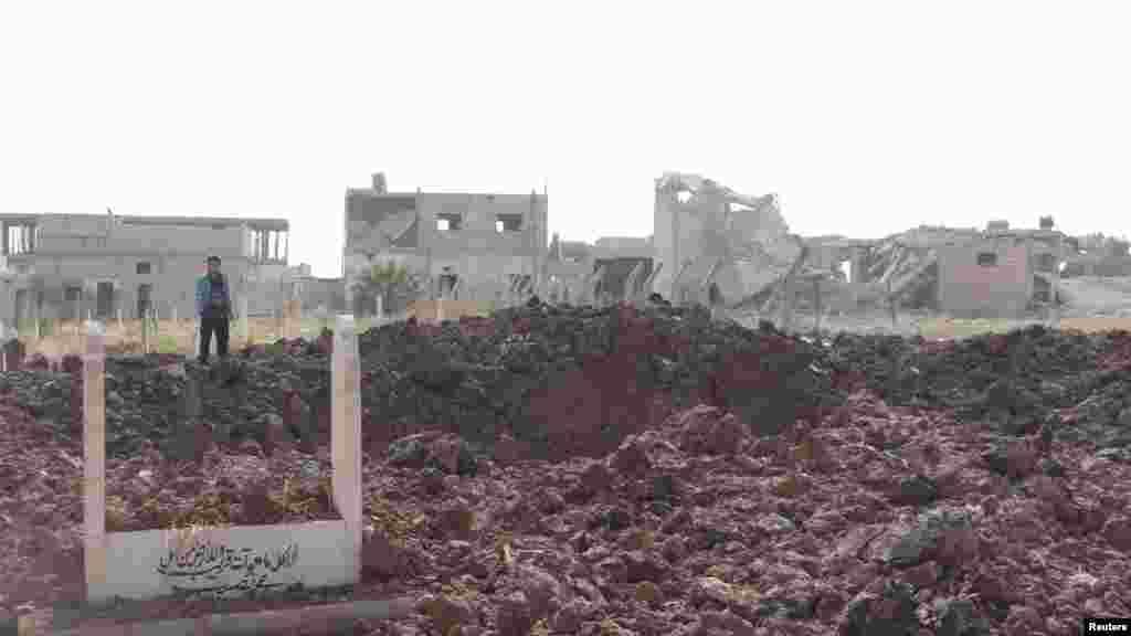 ساکنان در نزدیکی ساختمان ها و قبرستان آسیب دیده پس از بمباران جتهای جنگنده نیروی هوایی سوریه، وفادار به بشار اسد، رئیس جمهور سوریه، بشار اسد، در تفتناز در نزديکی ادليب، ۴ نوامبر، ۲۰۱۲.