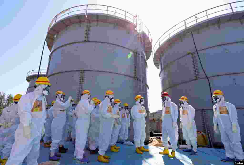 Japan's Prime Minister Shinzo Abe (in red helmet), wearing a protective suit and mask, is briefed about tanks containing radioactive water by Fukushima Daiichi nuclear power plant chief Akira Ono in Okuma, Sept. 19, 2013.