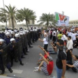 Anti-government protesters shout slogans at riot policemen as they block a road in Manama, Bahrain, March 13, 2011