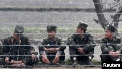 지난해 4월 압록강변에 북한 군인들이 앉아있다. 신의주에 접한 중국측 지역에서 촬영한 사진이다.
