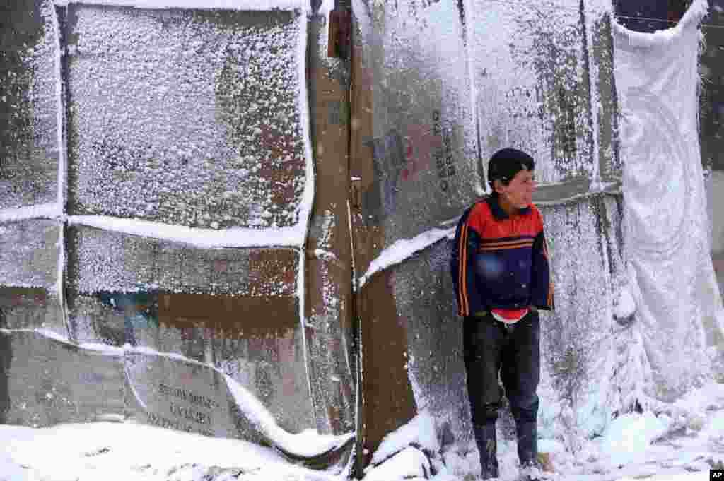 A Syrian refugee boy stands outside his tent in a camp for Syrians who fled their country's civil war, in the Bekaa valley, eastern Lebanon, as a heavy snowstorm batters the region.