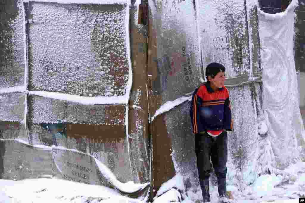 Một cậu bé người tỵ nạn Syria đứng bên ngoài lều của mình trong một trại tỵ nạn cho người Syria rời nước lánh cuộc nội chiến ở thung lũng Bekaa, miền đông Libăng, trong khi một cơn bão tuyết nặng ập vào khu vực.