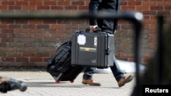 FILE - An inspector from the Organization for the Prohibition of Chemical Weapons (OPCW) arrives to begin work at the scene of the nerve agent attack on former Russian spy Sergei Skripal, in Salisbury, Britain, March 21, 2018. An OPCW team will begin coll