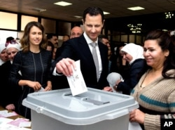 This photo released on the official Facebook page of Syrian Presidency, shows Syrian President Bashar Assad casting his ballot in the parliamentary elections, as his wife Asma, left, is standing next to him, in Damascus, Syria, Wednesday, April 13, 2016.