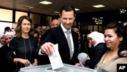 Syrian President Bashar al-Assad casts his ballot in parliamentary elections as wife Alma, left, observes, in Damascus, April 13, 2016. The photo was posted on the official Facebook page of the Syrian Presidency.