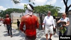Des touristes regardent passer des fidèles, ensanglantés après l'auto-flagellation lors du traditionnel crucifiement philippin du Vendredi Saint à San Pedro Cutud, province de Pampanga, Philippines, le 29 mars 2013.