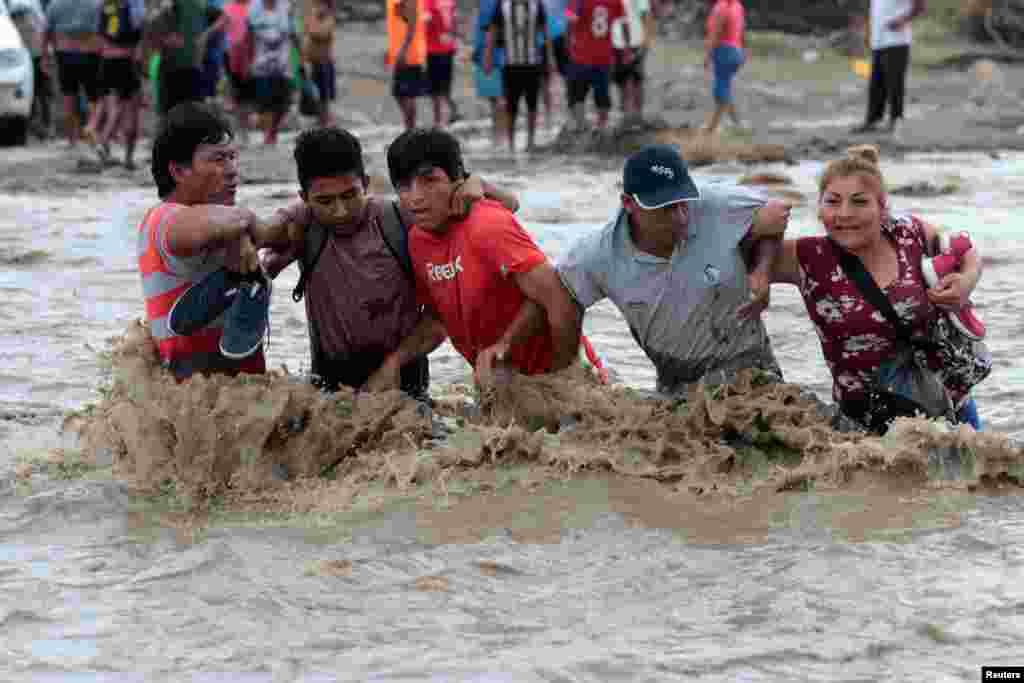 """بعد از این که سیل و لغزش زمین در شهر تروخیو در پرو باعث شد که پل رودخانه """"ویرو"""" فرو بریزد، ساکنان این شهر مجبور هستند از داخل رودخانه رد شوند."""