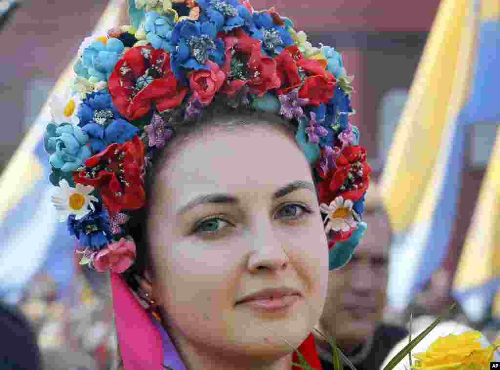 A Ukrainian, dressed in traditional embroidered clothing, attends an event at a monument to the revered national poet Taras Shevchenko marking the 203th anniversary of his birth, in Kyiv.